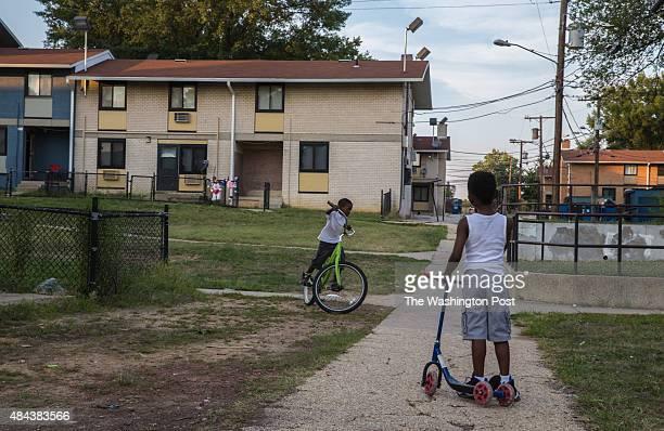 Children ride their scooters in Woodland Terrace a public housing complex in Southeast Washington where police have increased their presence August 3...