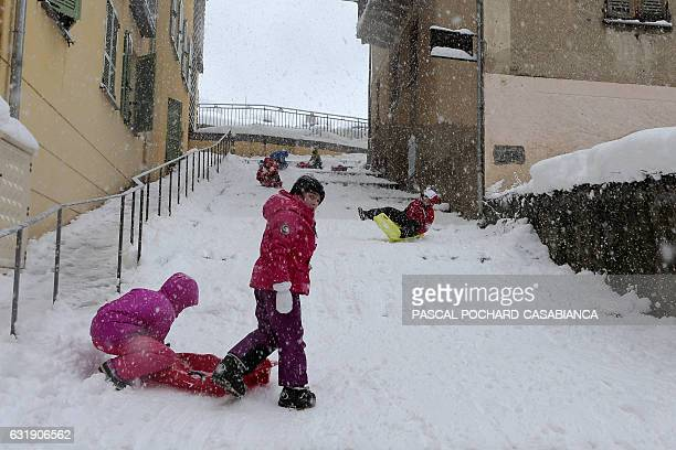 Children ride their sledges down snow covered stairs Corte covered by snow on January 17 2017 on the French Mediterranean island of Corsica / AFP /...
