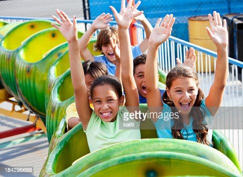 Children riding a green roller coaster