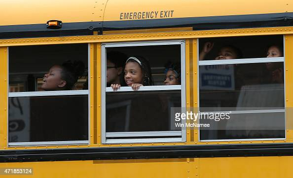 Children riding home from school on a school bus watch as Baltimore residents celebrate at the corner of West North Avenue and Pennsylvania Avenue...