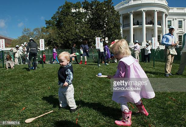 Children roll eggs at the annual Easter Egg Roll at the White House in Washington DC on March 28 2016 / AFP / Nicholas Kamm