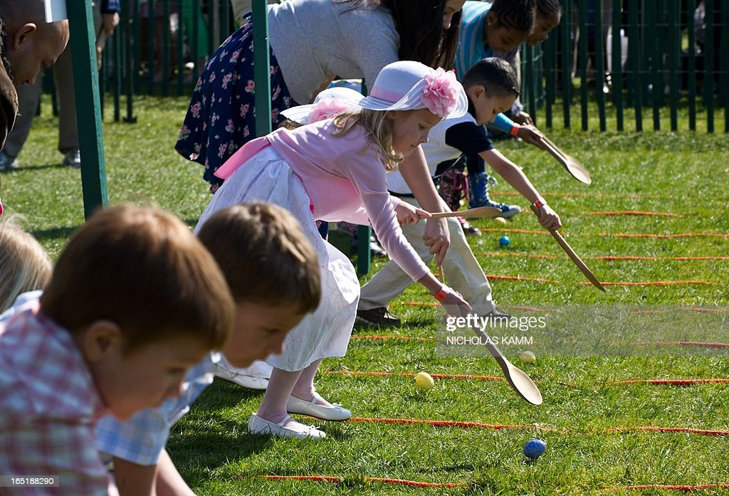 Children roll eggs on the South Lawn during the annual White House Easter Egg Roll in Washington on April 1, 2013. AFP PHOTO/Nicholas KAMM