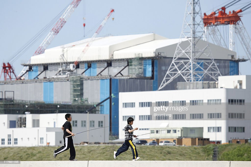 Children run along a breakwater at a fishing port near the reactor building for Electric Power Development Co.'s (J-Power) Oma nuclear power plant under construction in Oma Town, Aomori Prefecture, Japan, on Saturday, June 25, 2011. Over the 29 years since the nuclear plant was proposed, Oma has received almost 11 billion yen in subsidies, said Kenichi Ito, a town planning official. In Oma and other Aomori towns, the grants helped offset declining revenues that threatened the survival of rural communities, officials said. Photographer: Kiyoshi Ota/Bloomberg via Getty Images