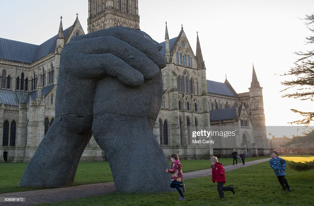 Children run around Sophie Ryder's sculpture The Kiss, that has been installed in the grounds of Salisbury Cathedral as part of an exhibition by the artist on February 10, 2016 in Salisbury, England. The solo exhibition, Relationships, featuring life-sized Minotaurs, Lady Hares and giant 20ft high clasped hands installed in and around the historic Cathedral, opens on February 12 and runs until July 3