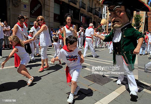 Children run away from a 'Kiliki' during San Fermin festival's Comparsa de gigantes y cabezudos on July 12 2011 in Pamplona Spain Pamplona's famous...