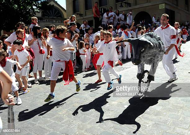 Children run during the 'encierro txiki' of the San Fermin Festival in Pamplona northern Spain on July 9 2015 The festival is a symbol of Spanish...