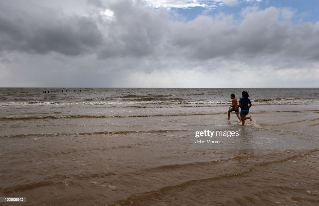 Children run into the Gulf waters ahead of the arrival of Hurricane Isaac on August 28 2012 in Bay St Louis Mississippi Many residents of the area...