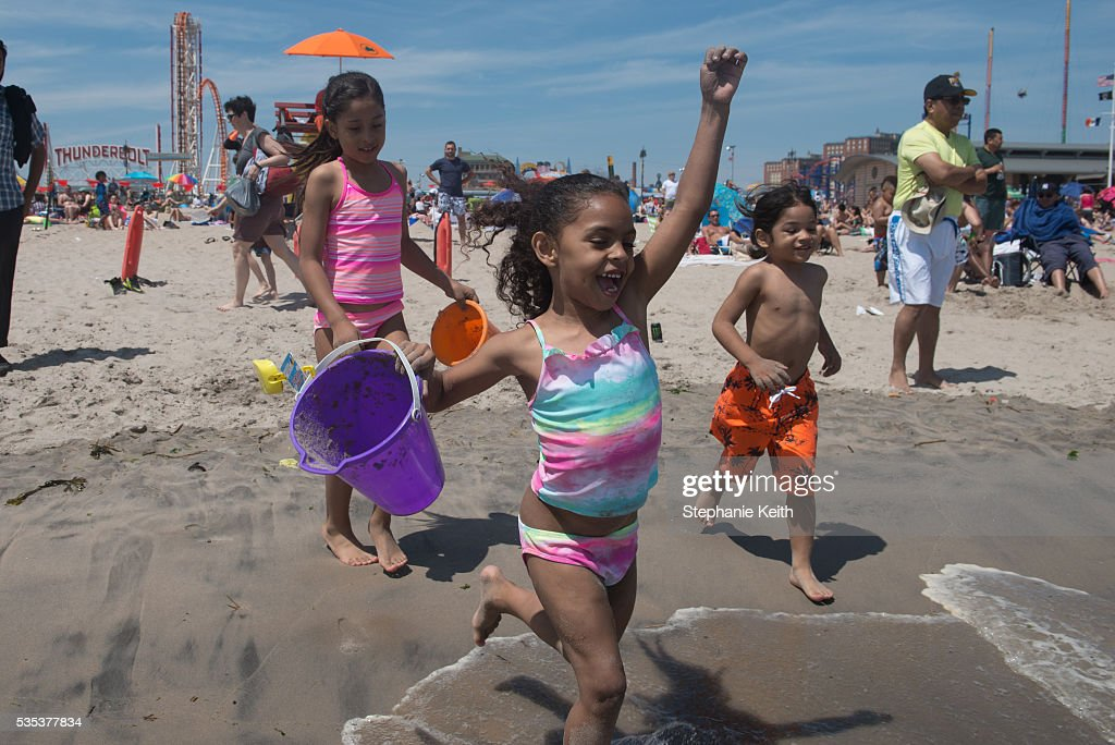 Children run into the ocean during a day at the beach in Coney Island on May 29, 2016 in the Brooklyn borough of New York City. New York City is experiencing higher than average temperatures for the holiday weekend.