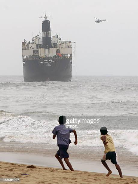Children run on the beach as an Indian Coast Guard HAL Chetak helicopter flies over the oil tanker ship Pratibha Cauvery during search operations...