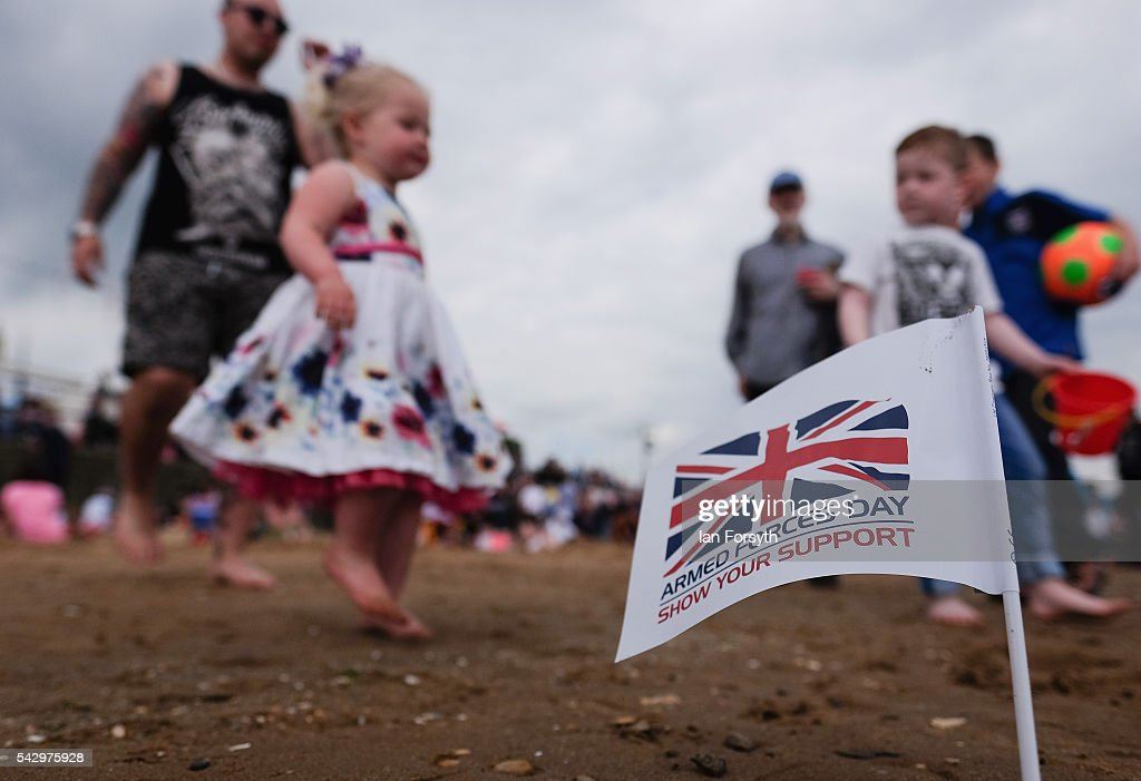 Children run past a flag planted in the sand during the Armed Forces Day National Event on June 25, 2016 in Cleethorpes, England. Armed Forces Day is an annual event that gives an opportunity for the country to show its support for the men and women in the British Armed Forces.