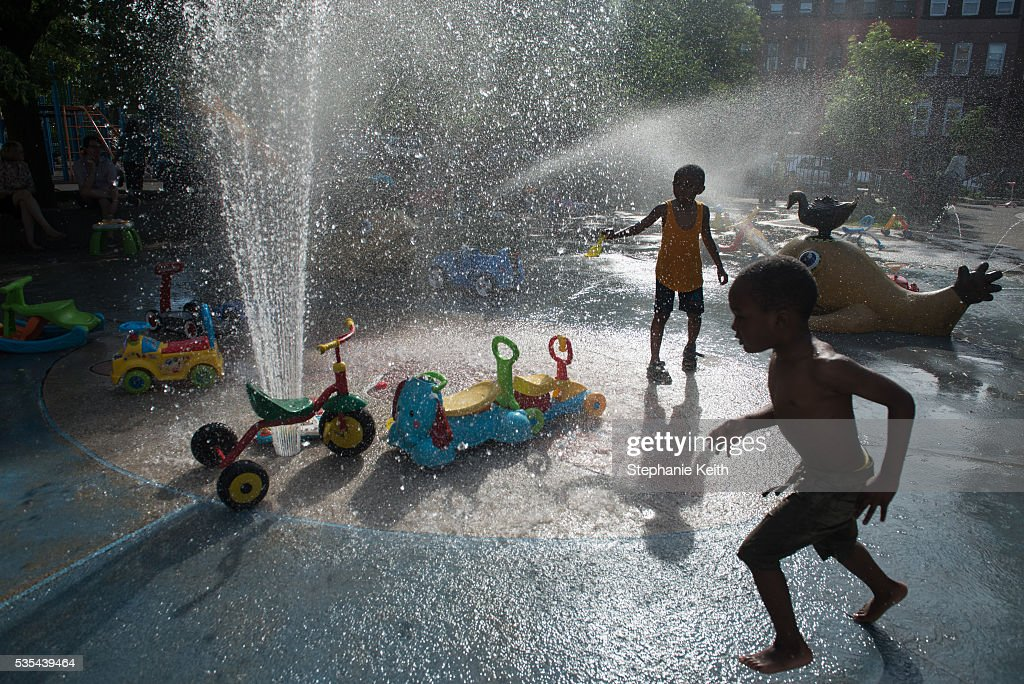 Children run through the sprinklers at a playground on May 29, 2016 in the Brooklyn borough of New York City. New York City is experiencing higher than average temperatures for the holiday weekend.