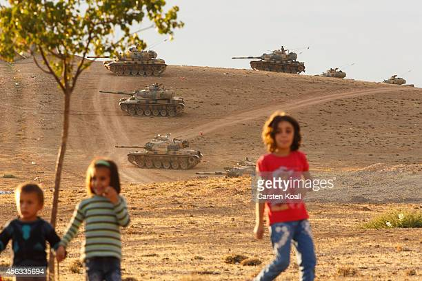 Children run while tanks from the Turkish Armed Forces are dispatched to the Turkish Syrian border as clashes intensified with Islamic State of Iraq...