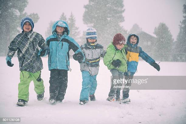 Children running and playing in the snow during a storm