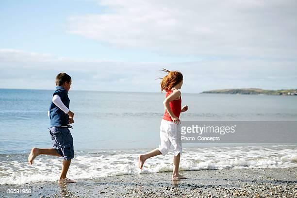 Enfants courir pieds nus sur la plage