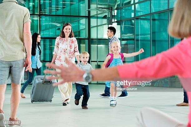 Children running excitedly towards grandmother