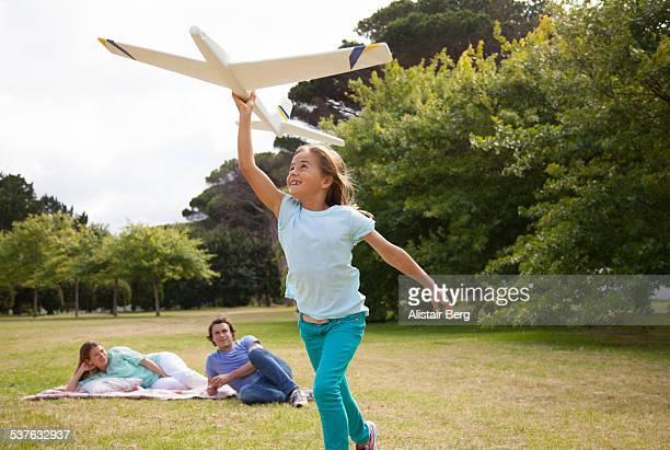 Children running in park with plane