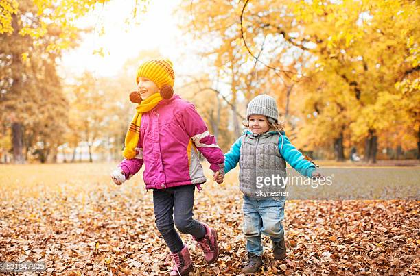 Children running in the park in autumn.