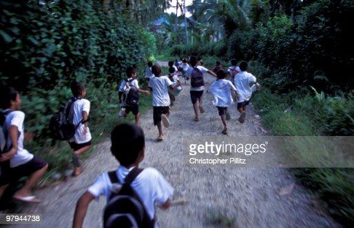 Children running in village lane : Stock Photo