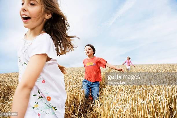 Children running in wheat field