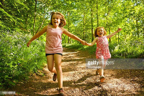 Children running laughing down forest trail