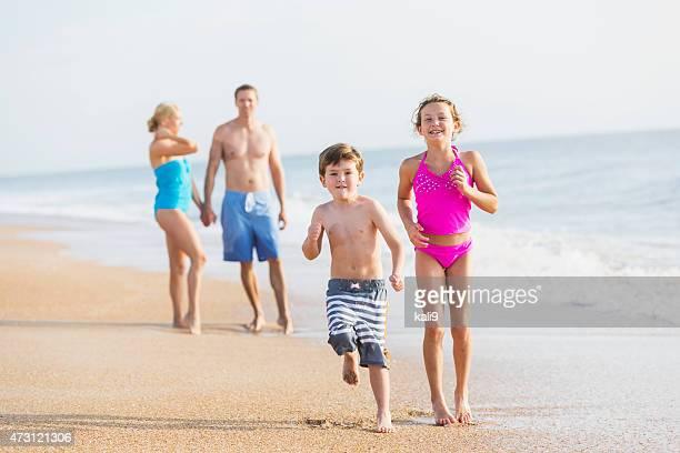 Children running on beach, parents watching