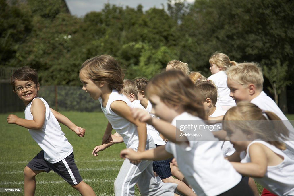 Children (5-7) running on field : Stock Photo