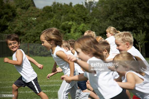 Children (5-7) running on field