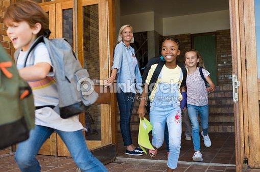 Children running outside school : Stock Photo
