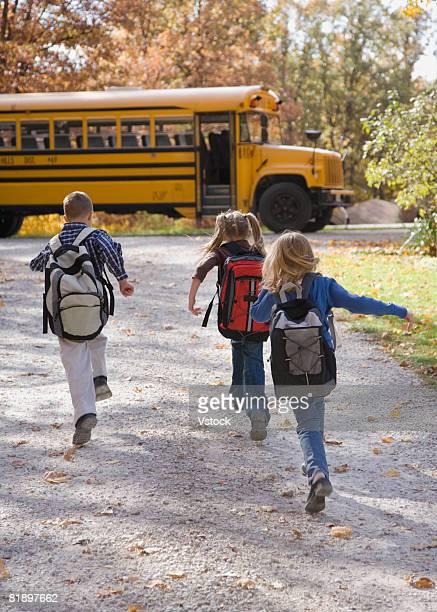 Children running towards school bus