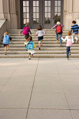 Children running up school steps