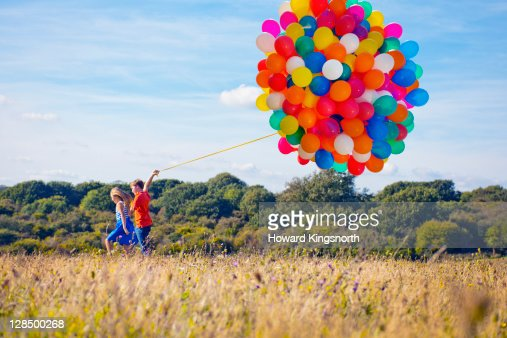 2 children running with bunch of balloons : Stock Photo