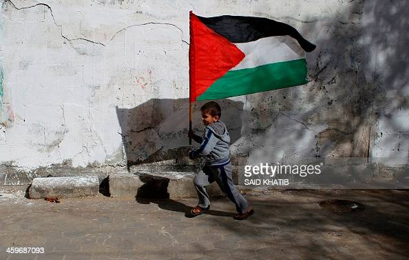 A children runs with the Palestinian flag as friends and relatives prepare for the release of prisoner Ramy Barbakh outside his home in Khan Yunis in...