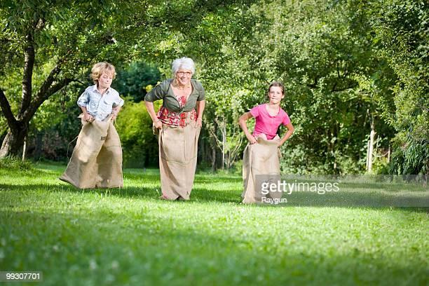 Children sack racing with grandmother