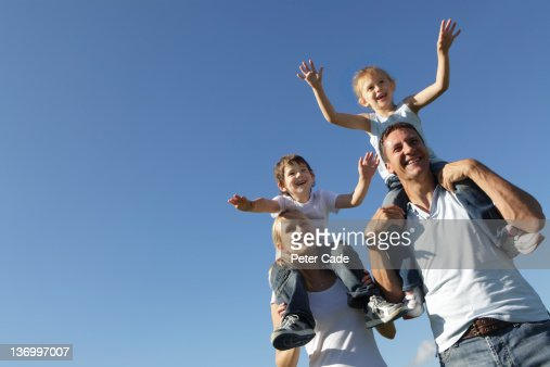 children sat on parents shoulders, blue sky : Stock Photo