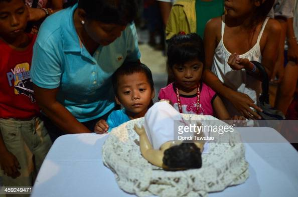 TACLOBAN LEYTE PHILIPPINES DECEMBER 24 Children say prayers before an effigy of the child Jesus on Christmas Eve on December 24 2013 in Palo Leyte...