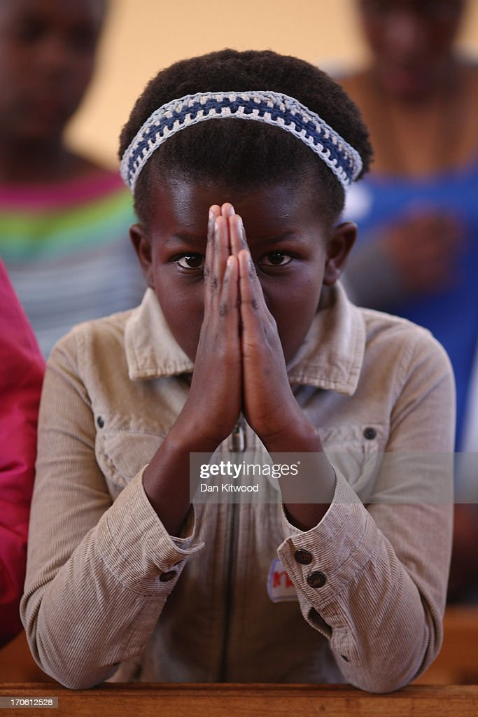 Children say prayers for Nelson Mandela as part of a youth service at the Holy Cross Anglican Church in Soweto on June 15, 2013 in Johannesburg, South Africa. It has been reported that he is responding better to treatment for a recurring lung infection.