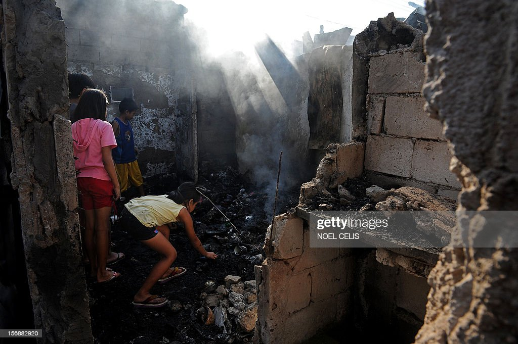 Children search for salvageable materials amongst the burnt debris of destroyed houses in Manila on November 24, 2012 after an overnight fire razed a slum area. Three children died during the fire and almost 150 people were affected according to local media report.