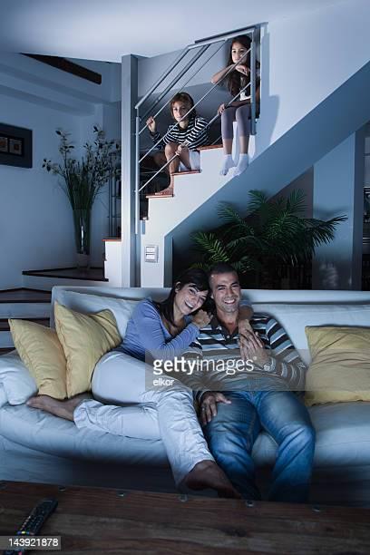Children secretly watching TV after bedtime behind parents back.