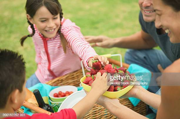 Children (7-8) selecting strawberries from bowl held by mother
