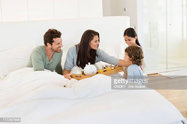 Children serving tea to their parents on the bed