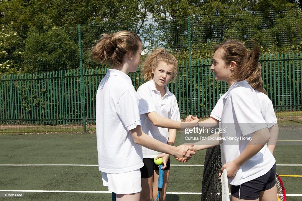 Children shaking hands at tennis match : Stock Photo