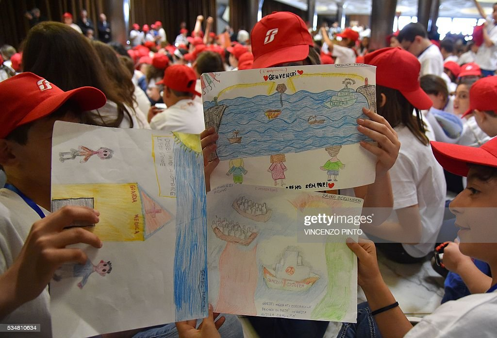 Children show drawings depicting migrants during a meeting of Pope Francis with 400 children from the south of Italy, Calabria, including children of migrants, on May 28, 2016 at the Vatican. / AFP / VINCENZO