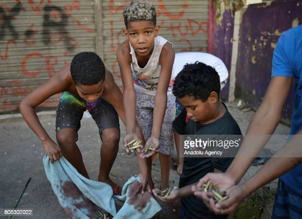 Children show spent bullet casings and a blood stained towel after a police operation at the Mangueira favela in Rio de Janeiro Brazil on June 30 2017