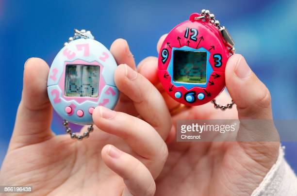 Children show their 'Tamagotchi' electronic pet on October 25 2017 in Paris France Tamagotchi is a virtual electronic animal which means 'cute little...