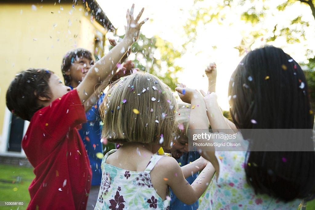 Children showered in falling confetti : Stock Photo