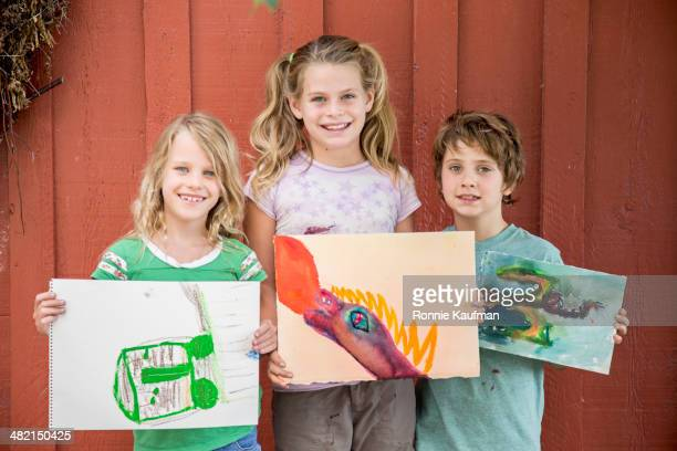 Children showing off drawings