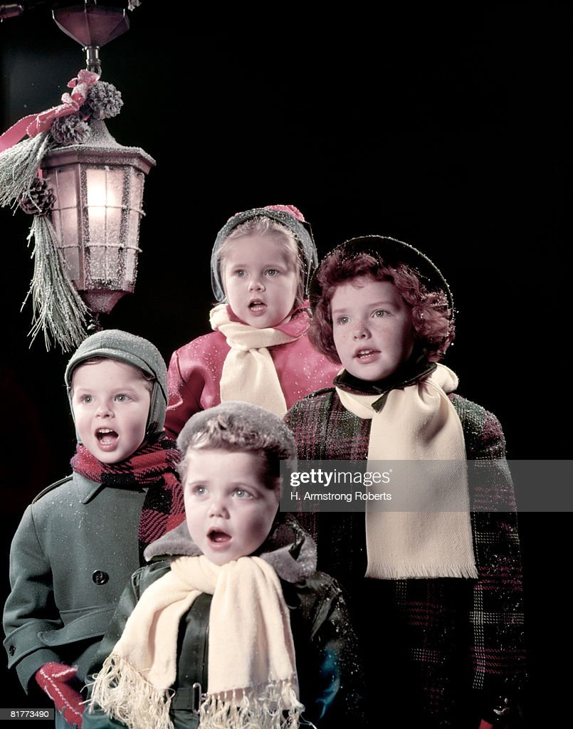 4 Children (Boys And Girls) Sing Carols Under Lantern In Front Of Dark Background. They Are Wearing Winter Hats, Coats, And Scarf.
