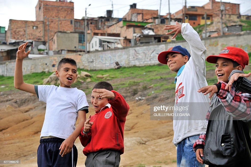 Children sing hip hop on April 26, 2016 in the municipality of Soacha, on the outskirts of Bogota, where an NGO promotes activities among some 300 at-risk children and teenagers. Through hip hop, graffiti art and other activities, the Proyecto de vida (Life Project) foundation - funded by Luxembourg NGO Children of Hope - is seeking to keep children in vulnerable situation away from drug addiction and crime. / AFP / GUILLERMO