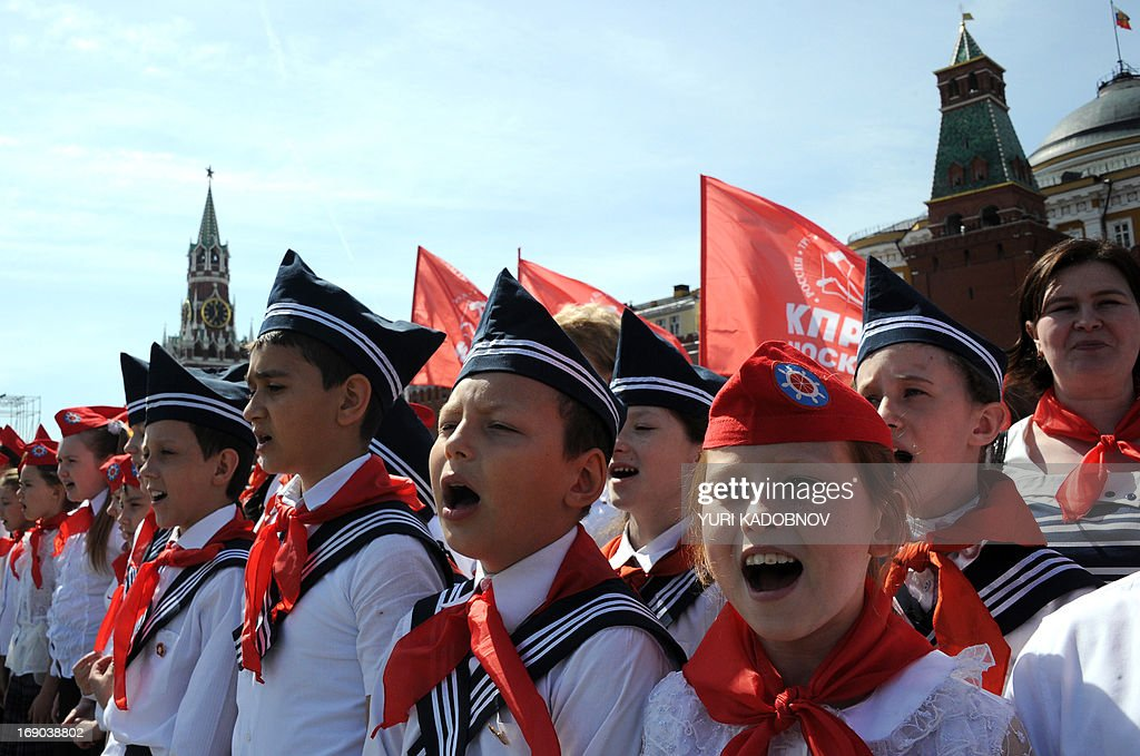 Children sing songs after veterans of Russian Communist Party tied red scarves around their necks, symbolizing their initiation into the Young Pioneer Youth communist group, created in the Soviet Union for children 10-14 years old, in Moscow's Red square on May 19, 2013 during the organization's celebration day. Some three thousands pioneers took part in the ceremony.
