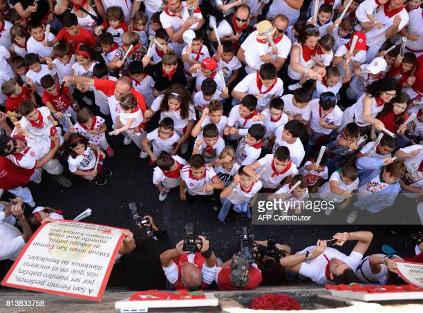 Children sing to an image of San Fermin prior to running the 'Encierro Txiki' during the San Fermin Festival in Pamplona northern Spain on July 13...